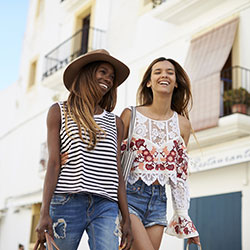 Two friends on vacation together walking down a street enjoying themselves.