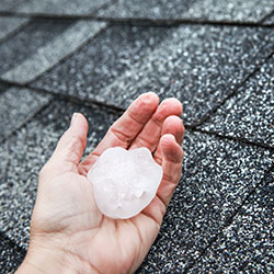 A large hailstone in a person's hand against the back drop of the home's roof.