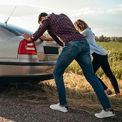A man and woman pushing their car that has broken down..