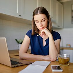 A woman deep in thought sitting at her desk looking over her computer screen.